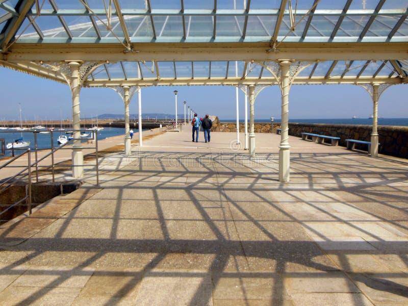 Toeristen lopen langs Dun Laoghaire Pier in Ierland royalty-vrije stock foto