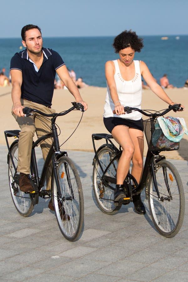 Toeristen met fietsen op een stadsstrand stock fotografie