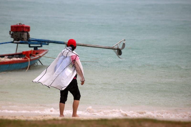 Toeristen met paraplu en regenjas of Reddingsvesten op het strand royalty-vrije stock foto's