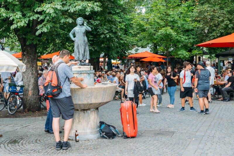 Toeristen naast standbeeld van actrice Liesl Karl Town in München ` s Viktualienmarkt stock fotografie
