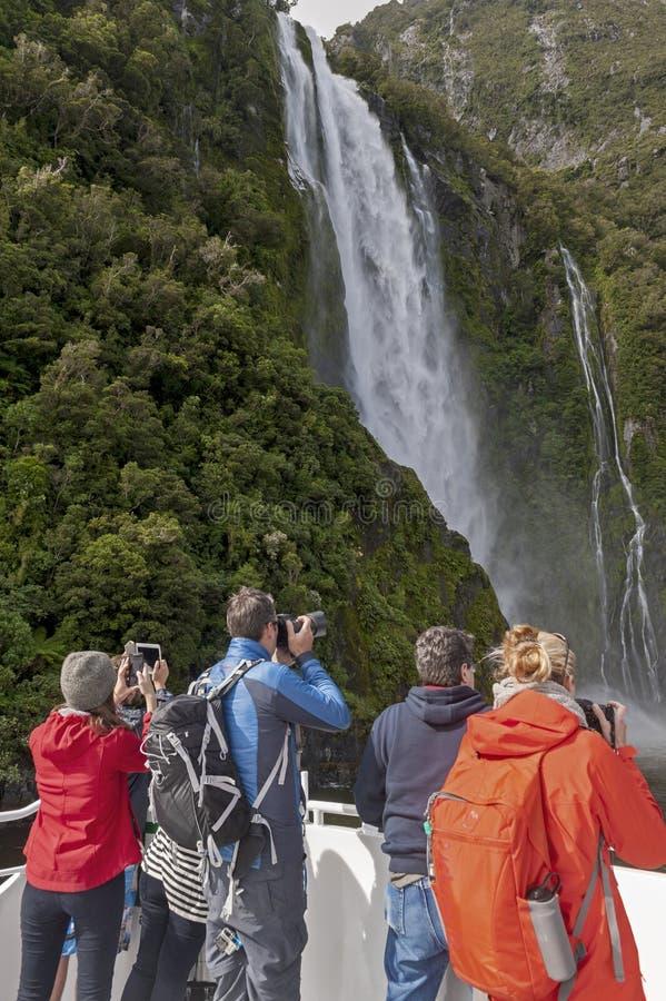 Toeristen op de kruisboot die Stirling Falls, Milford-Geluid, Fiordland, Zuideneiland benaderen van Nieuw Zeeland royalty-vrije stock foto