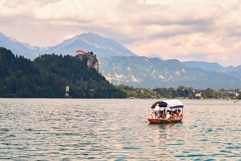 Toeristen op de Pletna-boot die over het Afgetapte meer varen stock fotografie