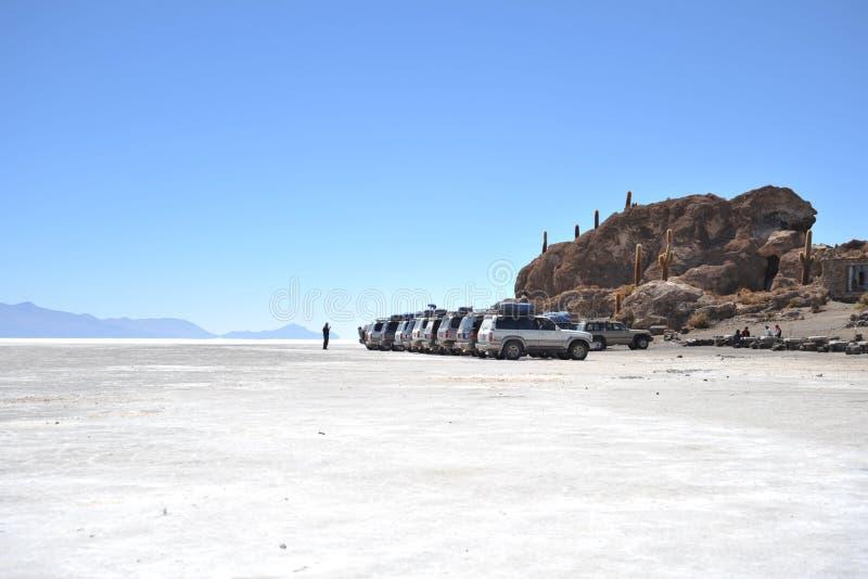 Toeristen op de zoute vlakten van Uyuni stock foto