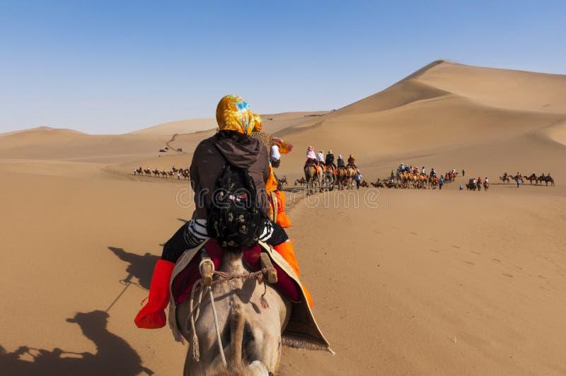 Toeristen op een kameelcaravan in de duinen rond de stad van Dunhuang, in de oude Zijdeweg, in China royalty-vrije stock afbeeldingen