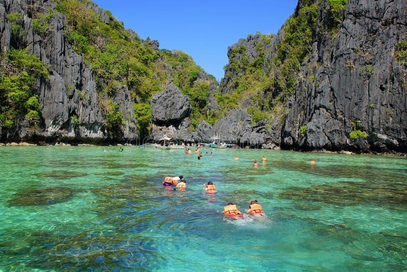 Toeristen in reddingsvesten die bij lagune zwemmen. royalty-vrije stock afbeelding