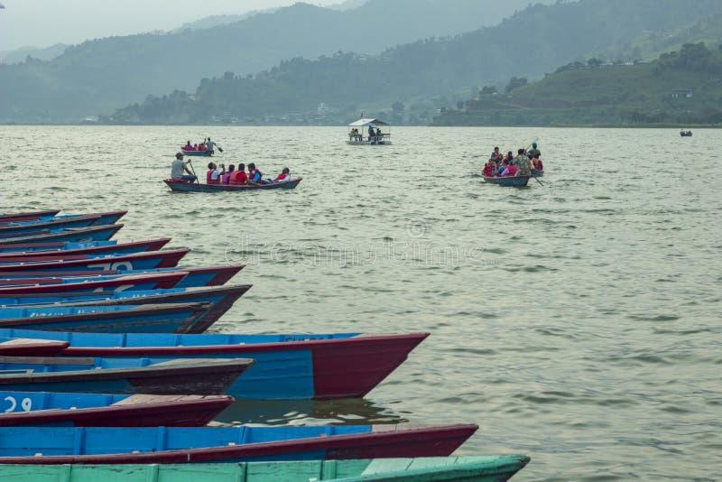 toeristen in rode reddingsvesten in een het roeien boot op een achtergrond van groene bergen in de mist royalty-vrije stock afbeelding