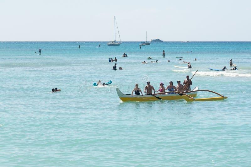 Toeristen van kust van Waikiki in traditionele kano stock afbeeldingen