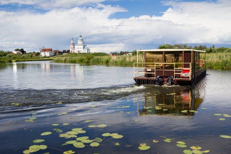 Toeristenboot die onderaan de rivier met witte kerk op de achtergrond gaan stock foto