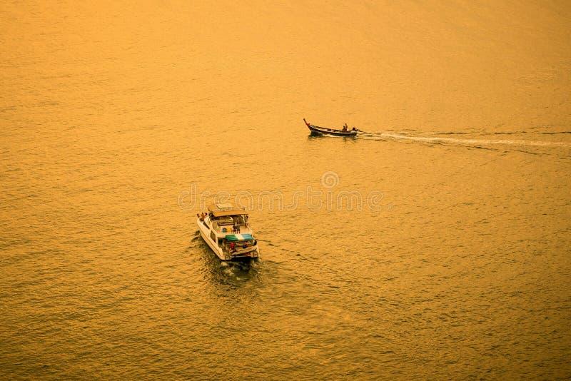 Toeristenboot met kleine boot in het gouden overzees royalty-vrije stock foto