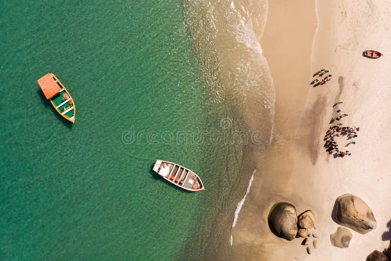 Toeristenboten die op een eilandstrand aankomen stock foto