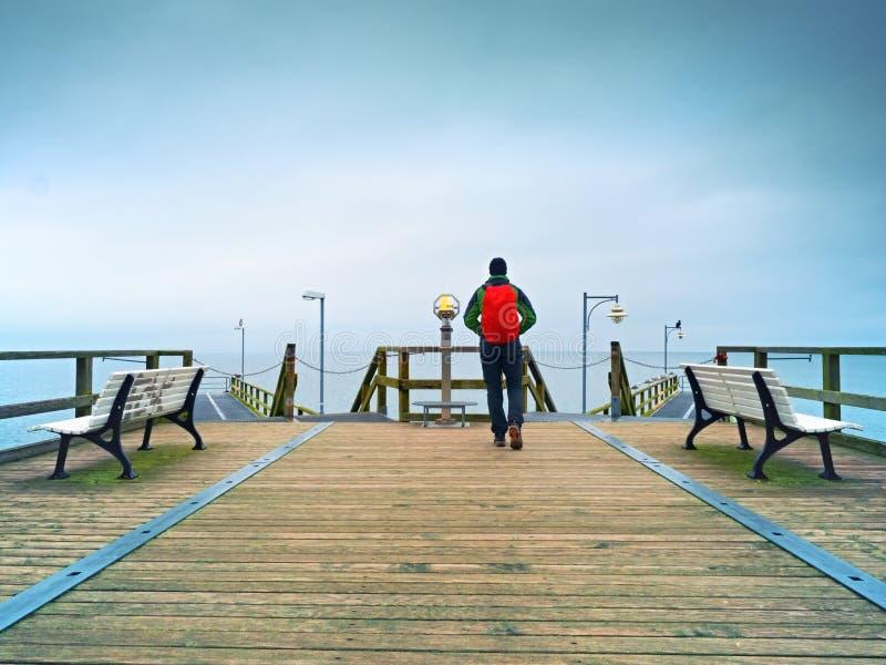 Toeristengang in de herfstmist op houten pijler boven overzees Regenachtige dag stock foto's