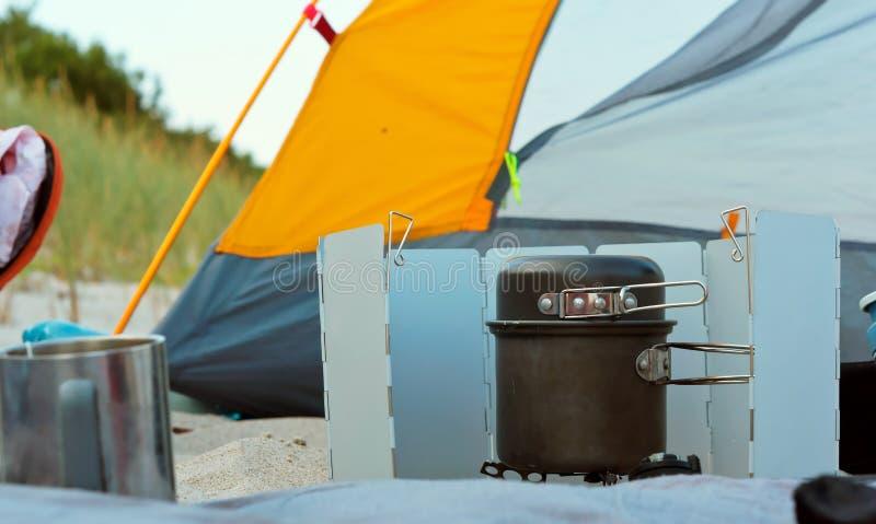 Toeristengasfornuis en gele tent, kamperende brander en tent stock afbeelding