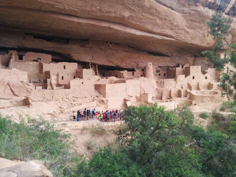 Toeristengroep bij complex van oude ruïnes in Mesa Verde National Park royalty-vrije stock afbeeldingen
