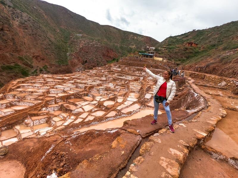 Toeristenmeisje die de zoute vijvers overwegen in Maras Peru stock foto's