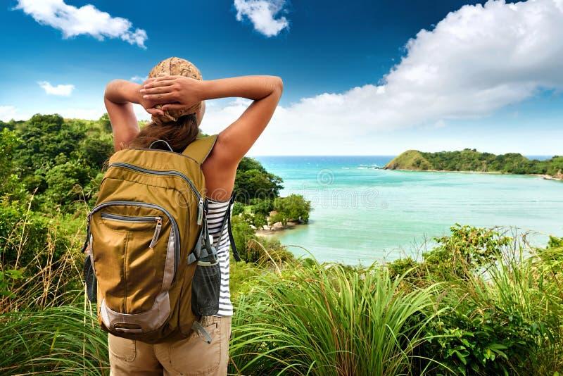 Toeristenmeisje die van mening van mooie heuvels en overzees, travelin genieten royalty-vrije stock afbeeldingen