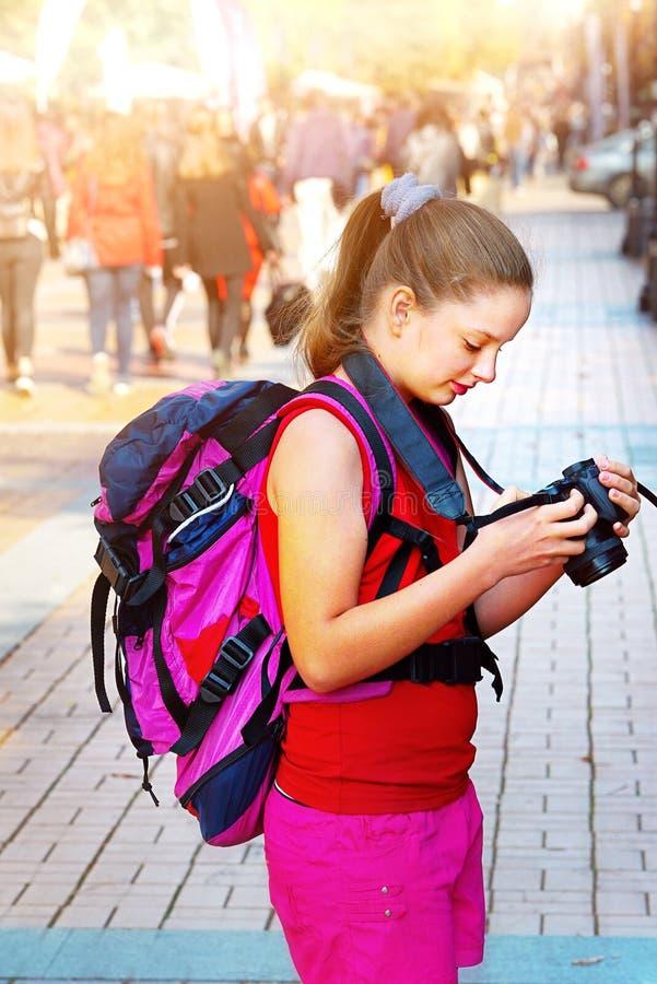 Toeristenmeisje met rugzak die beelden op digitale camera nemen royalty-vrije stock afbeelding
