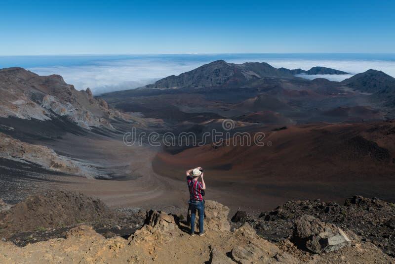 Toeristenmens die foto's van de vallei van de vulkaanberg vanaf de bovenkant op Groot Eiland, Hawaï nemen stock afbeelding