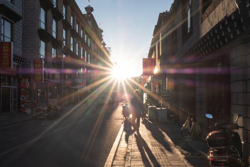 Toeristenmens die in traditionele steeg bij zonsondergang lopen stock foto