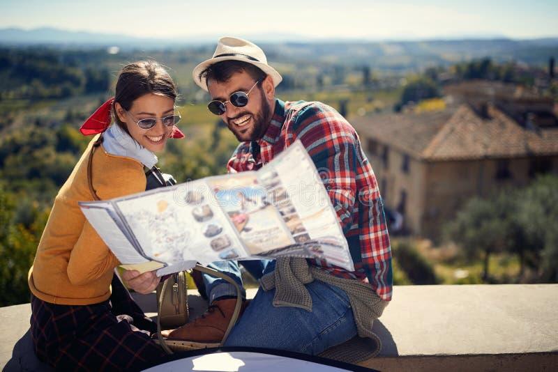 Toeristenmens en meisje die kaart gebruiken als gids op reistijd stock fotografie