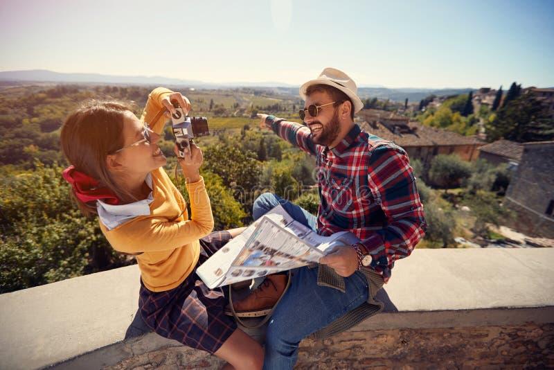 Toeristenmens en meisje gebruikend kaart als gids op vakantietijd en nemend beeld royalty-vrije stock foto's