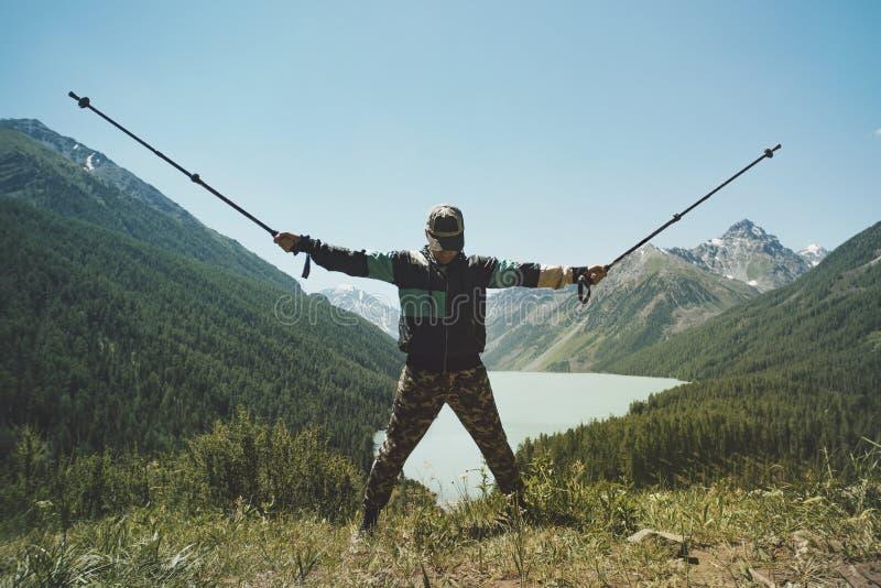 Toeristenmens met wandelstokken met zijn handen omhoog op bergheuvel dichtbij meer royalty-vrije stock fotografie
