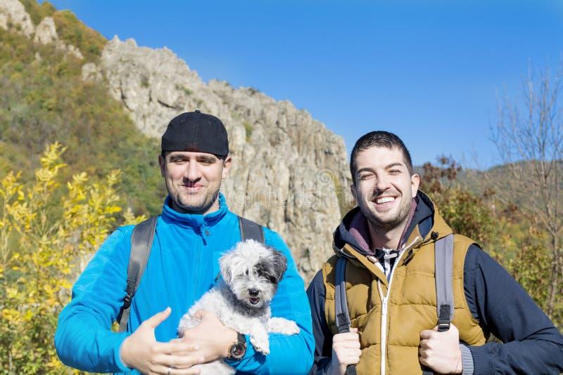 Toeristenmensen in de de herfstberg met hun hond royalty-vrije stock afbeelding