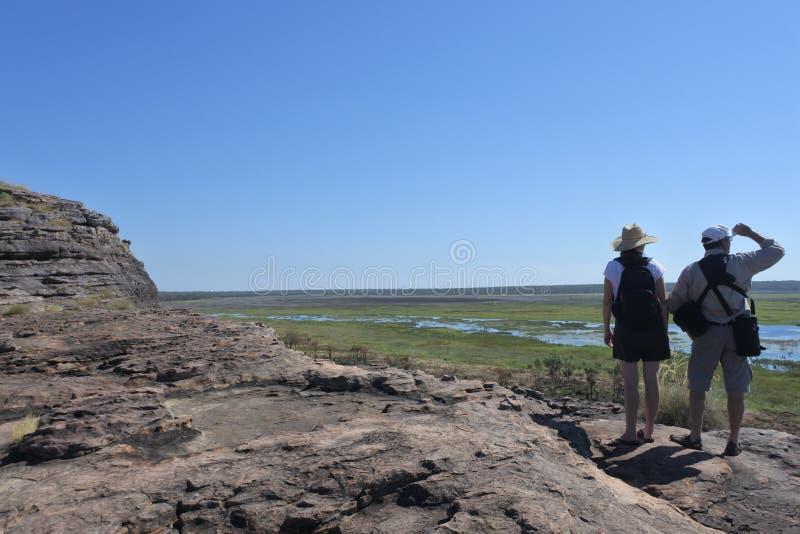 Toeristenpaar die bij Ubirr-de plaats van de rotskunst op Nationaal het Park Noordelijk Grondgebied van Kakadu wandelen van Austr stock afbeeldingen