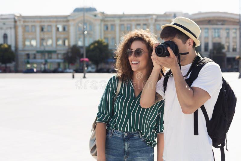 Toeristenpaar die foto's op camera op straat nemen stock afbeelding