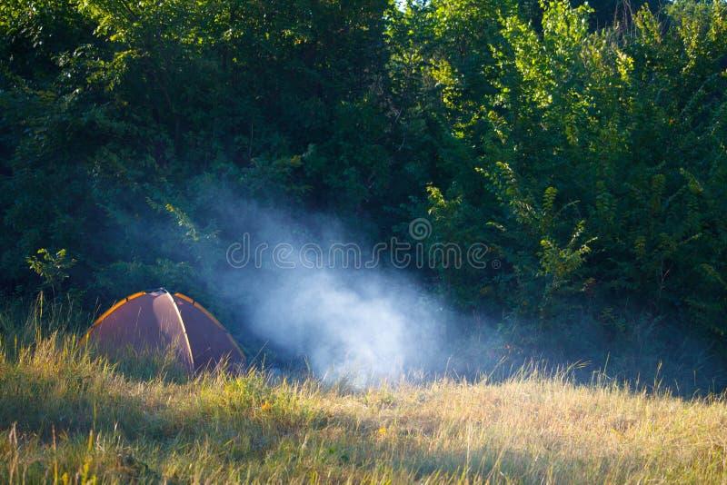 Toeristentent en rokend vuur op een gebied voor het bos bij zonsopgang stock fotografie