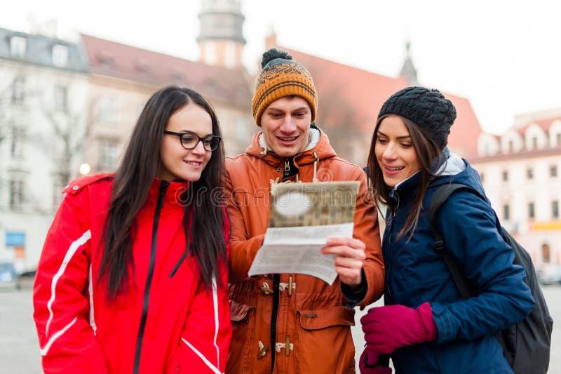 Toeristenvrienden die naar richtingen zoeken stock foto