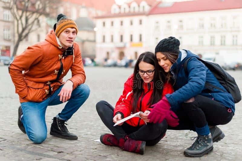 Toeristenvrienden die naar richtingen zoeken stock afbeeldingen