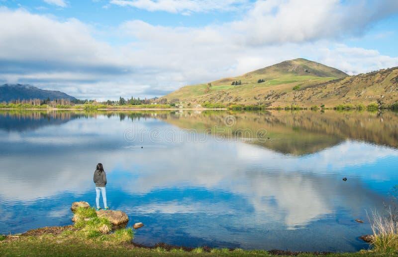 Toeristenvrouw die en zich aan spectaculaire mening van meer Hayes, Nieuw Zeeland bevinden kijken stock foto