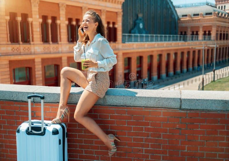 Toeristenvrouw die met groene smoothie op een celtelefoon spreken stock afbeeldingen