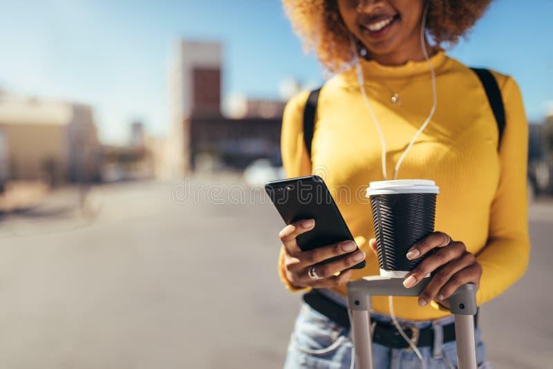 Toeristenvrouw die op straat lopen die mobiele telefoon bekijken royalty-vrije stock foto's
