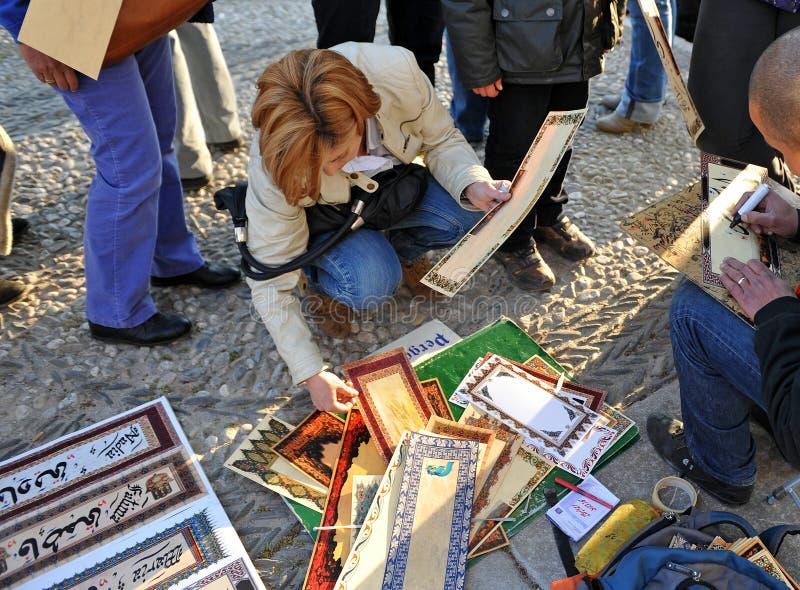 Toeristenvrouw die van verscheidene manuscripten van Arabische kalligrafie kiezen royalty-vrije stock foto's