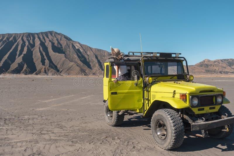 Toeristenvrouw die zich op deur gele vierwielige auto bevinden in woestijn stock afbeeldingen