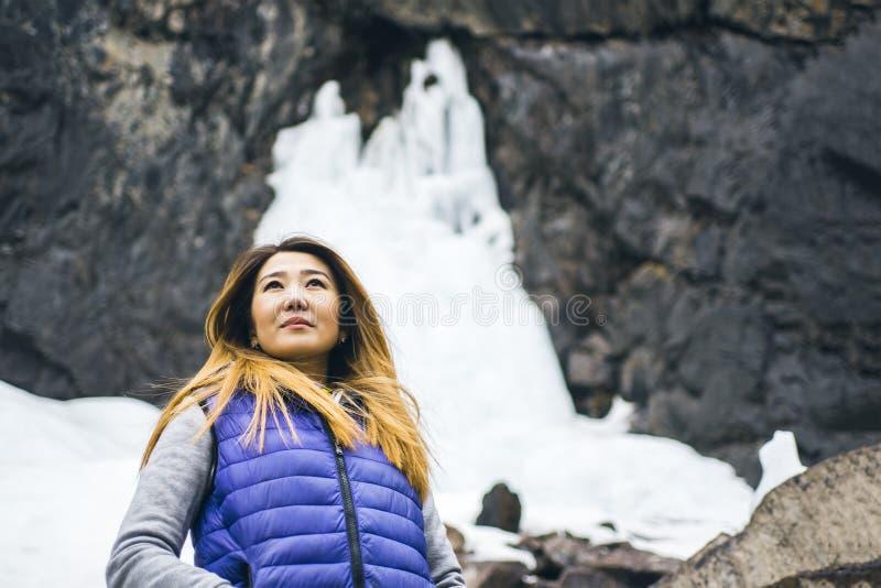 Toeristenvrouw en bevroren waterval royalty-vrije stock fotografie