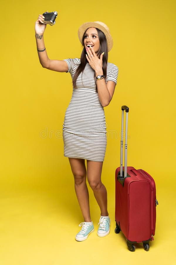 Toeristenvrouw met koffer in de zomer vrijetijdskleding die selfie maken die op gele achtergrond wordt geïsoleerd royalty-vrije stock afbeelding