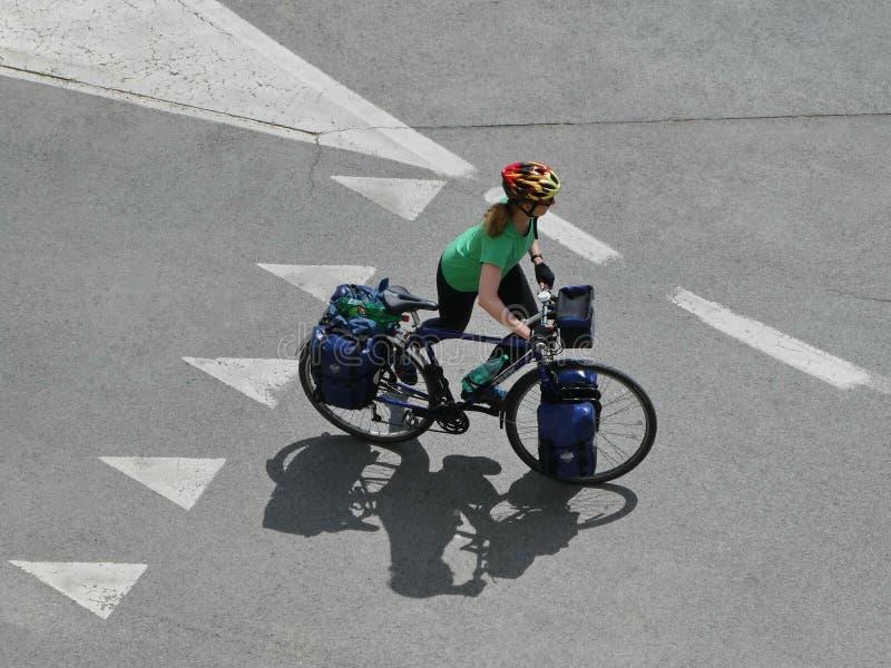 Toeristenvrouw op fiets die door de stad met pakketten op de fiets reizen stock foto