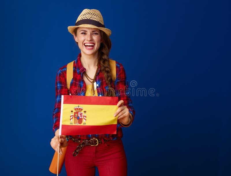 Toeristenvrouw tegen blauwe achtergrond die vlag van Spanje tonen stock afbeelding