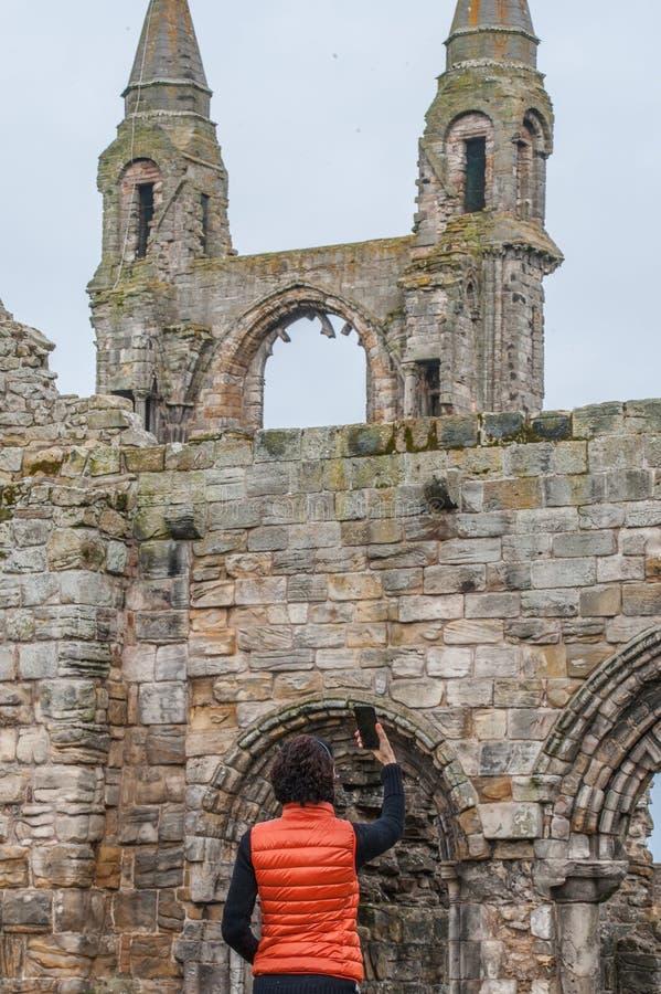 Toeristenvrouwen die selfie beelden van de ruïnes van St Andrews nemen stock afbeelding