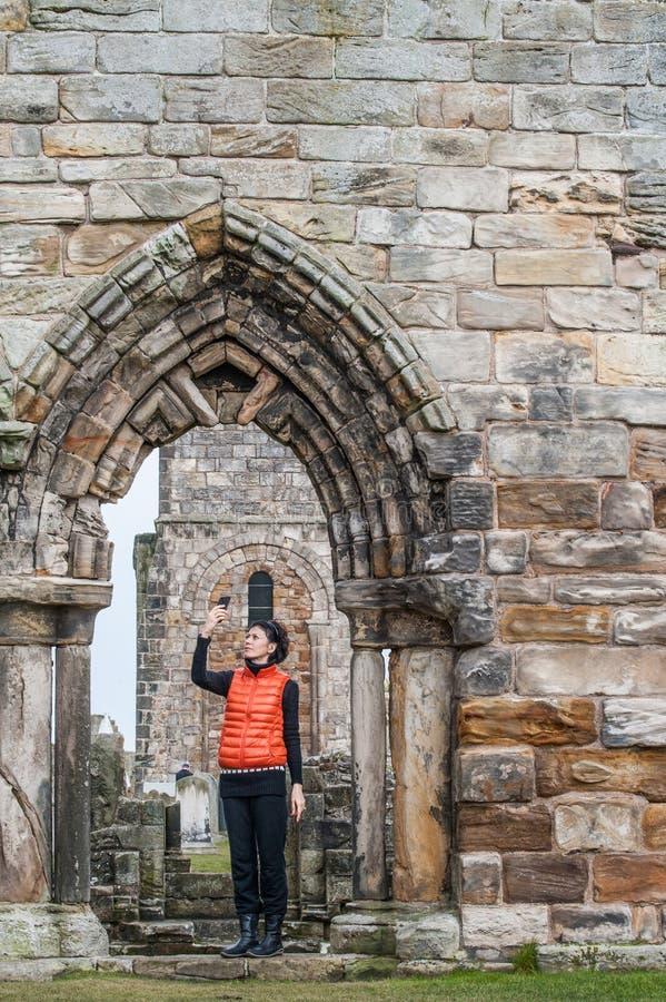 Toeristenvrouwen die selfie beelden van de ruïnes van St Andrews nemen stock afbeeldingen