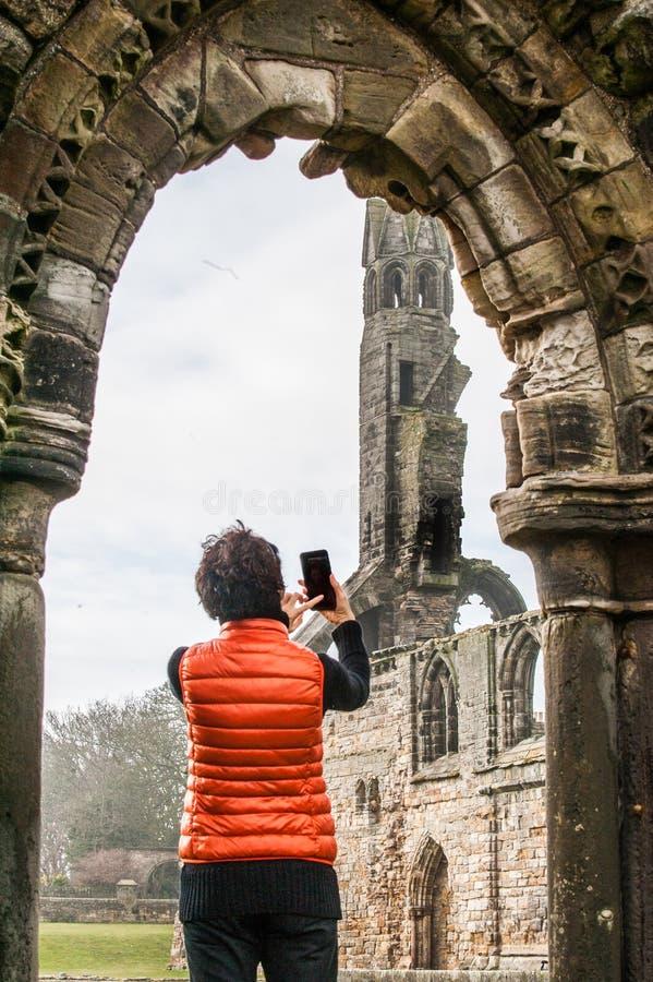 Toeristenvrouwen die selfie beelden van de ruïnes van St Andrews nemen stock fotografie