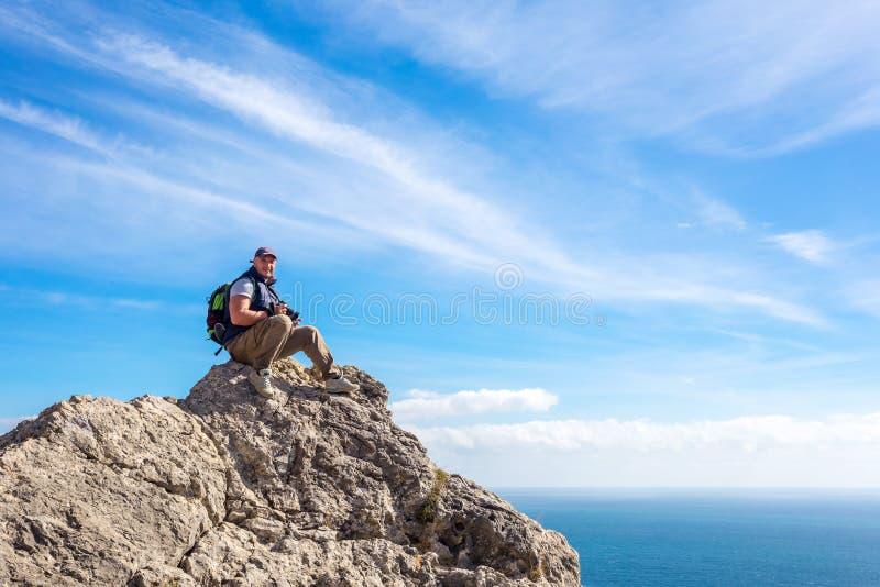 Toeristenzitting bovenop de berg die de afstand onderzoeken royalty-vrije stock afbeeldingen