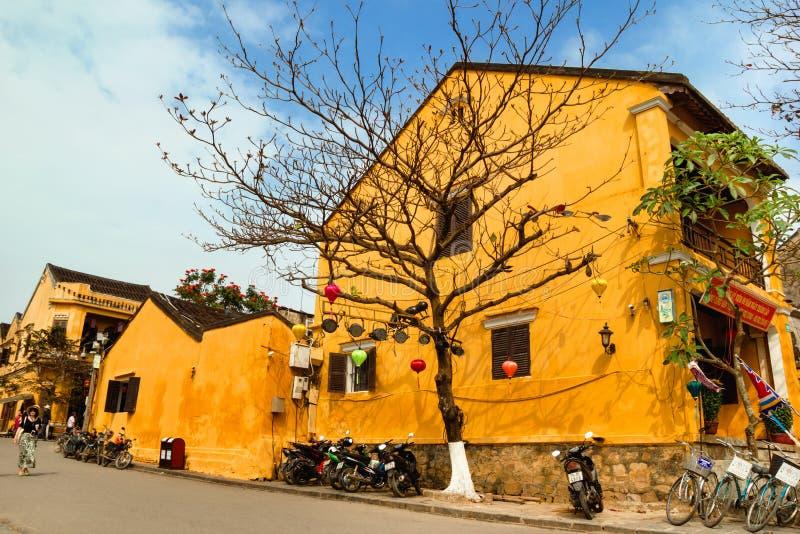 Toeristische straat in oude stad met gele huizen, grote boom, motoren en fietsen stock afbeeldingen