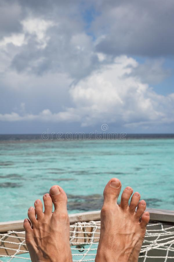 Toes with beautiful background. Male toes on the terrace from white knitted net above the ocean surface, against a tropical blue sky with clouds, Maldives royalty free stock photography