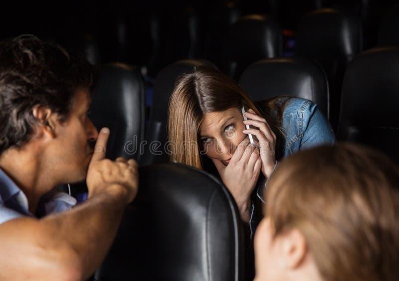 Toeschouwer die Shh-Uitdrukking geven aan Vrouw het Gebruiken stock foto