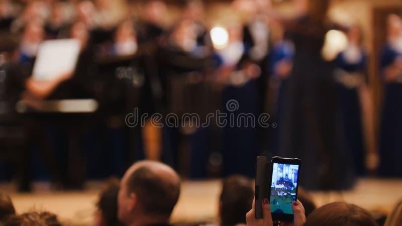 Toeschouwers bij overleg - mensen die prestaties op smartphone, muziekopera schieten royalty-vrije stock foto