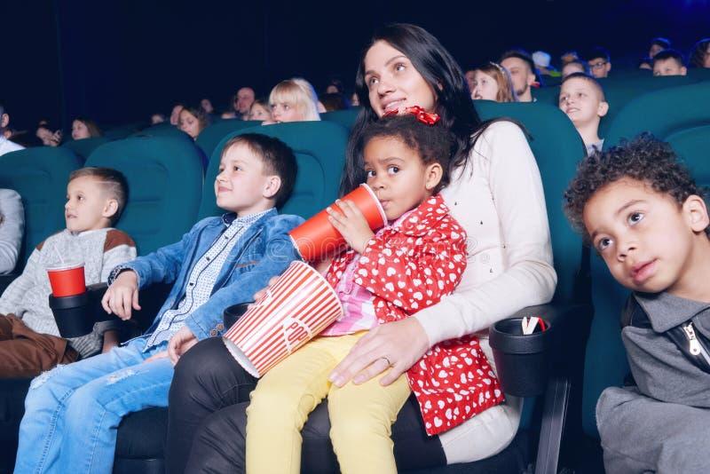 Toeschouwers die in filmtheater zitten en van film genieten, die snacks eten stock foto
