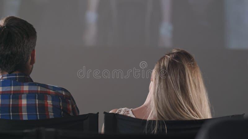 Toeschouwersmensen in een donkere bioscoop die op een film letten stock fotografie